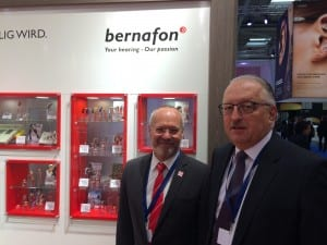 Bruno Keller and Erich Spahr stand in front of a hearing aid history exhibit that celebrates the company's 70th anniversary.