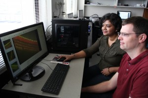 Assistant Professor of Biology Benjamin J. Perrin, PhD (R) and graduate student Pallabi Roy, MS (L) look at an image of auditory sensory hair cells in the Perrin lab in the School of Science at IUPUI.