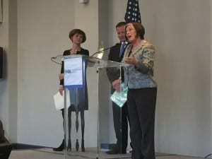 Carole Rogin (at podium) was honored for her nearly four decades of service to HIA and the hearing healthcare field, as Lucille Beck of the Department of Veterans Affairs and HIA President Brandon Sawalich look on.