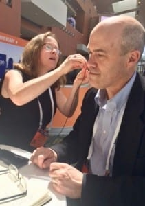 MED-EL's Acoustic Systems Manager Amanda O'Donnell demonstrates the ADHEAR system to HR Editor Karl Strom at the 2018 American Academy of Audiology Convention in Nashville.