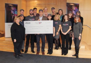 """Oticon President Gary Rosenblum celebrates success of the 2018 Oticon """"Hear in Pink"""" Campaign with the presentation of a $10,000 donation to National Breast Cancer Coalition representative Donna Duncan."""