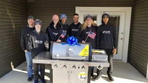 The Oticon team stands with the gas grill donated to McCloskey.